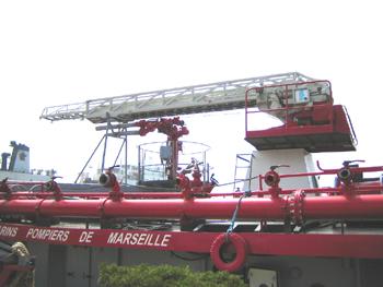 #218 - Long de près de 40 mètres. Propulsion par deux Voiht-Schneider entrainés par deux génératrices elles mêmes alimentées par deux moteurs diesel. Propulseur d'étrave au tiers avant. Quatre pompes d'un débit de 1 000 m3/h à 8 bar. Collecteurs latéraux de refoulement (une quinzaine de sorties par collecteur). Six lances Monitor. Bras élévateur (15 mètres au dessus du niveau de l'eau) et échelle pivotante. Vue d'une des deux collecteurs latéraux, de l'échelle pivotante et de la lance-canon eau-mousse sur plateforme. Photographie Vincent JURIENS - 2012