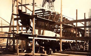 #115 - Mis en service en 1931 par la Chambre de commerce de Marseille et armé par les sapeurs-pompiers de Marseille (la 3ème compagnie dite compagnie du port) puis par les marins-pompiers de Marseille à partir de 1939. Retiré du service en 1964 et vendu pour démolition en 1965. 37 mètres de long sur 8 mètres de large. Pompe d'un débit de 1 200 m3/heure (12 kg). 5 lances Monitor dont une sur tourelle. Pompes d'épuisement débitant 3 000 m3/heure. Ce document est exceptionnel, les photographies de ce bateau-pompe sont très rares. On le voit ici en construction en 1930 sur les chantiers de la Société provençale de constructions navales (SPCN) à la Ciotat. Visiblement les membrures sont en cours d'installation. Ces dernières supporteront le bordage qui formera la coque Photographie Archives netpompiers - 1930