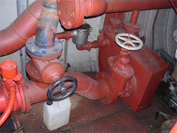 #493 - Long de 15.5 mètres. Capacité hydraulique de 4 000 l/min. Mis en service en 1982.  Vue d'une partie d'un des deux circuits de pompes. La pompe incendie Sides est à gauche. Au centre la voie d'aspiration extérieure, à droite la voie d'aspiration en pleine eau, chacune commandée par une vanne. En arrière-plan le circuit de refroidissement de moteur d'entrainement.  Photographie Xavier WATTIAU - 2006