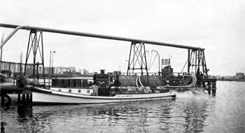#410 - Bateau-pompe en service à Amsterdam de 1930 à 1983. Long de 17 mètres. Capacité hydraulique de 6 000 l/min. Ici en position dans le Petroleumhaven: darse du port d'Amsterdam sur le canal de la Mer du Nord où s'effectue un stockage d'hydrocarbures. Photographie Amsterdam City Archives