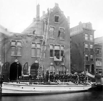 #413 - Bateau-pompe à vapeur en service à Amsterdam de 1875 à 1930. Long de 15 mètres. Capacité hydraulique de 4 000 l/min. Ici en exercice devant le centre de secours auquel il était affecté entre 1920 et 1940. Photographie Amsterdam City Archives