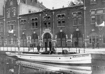 #414 - Bateau-pompe à vapeur en service à Amsterdam de 1875 à 1930. Long de 15 mètres. Capacité hydraulique de 4 000 l/min. Ici stationné devant le centre de secours auquel il était affecté. Remarquer le dinghy à l'arrière, une petite embarcation en bois utilisé pour des sauvetages ou pour l'évacuation du navire en cas d'avarie. Photographie Amsterdam City Archives