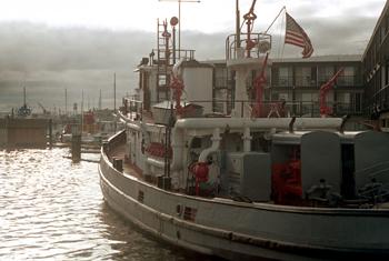 #298 - Ancien remorqueur portuaire de la Marine américaine Hoga. En service à Oakland de 1948 à 1996. Cette photographie montre bien le renforcement des équipements incendie apportés au moment de son affectation au port d'Oakland, en particulier les motopompes sur le pont arrière, l'ajout de lances canons et leurs alimentations... Photographie Nick DEWOLF - 1971