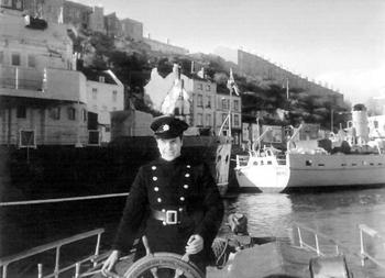 #520 - En service à Bristol de 1934 à 1973. Long de 17 mètres, capacité hydraulique de 5 000 l/min. Le pompier Clive Brain à la barre du bateau-pompe en 1968. Photographie Bristol Museums/Bristol Culture - 1968
