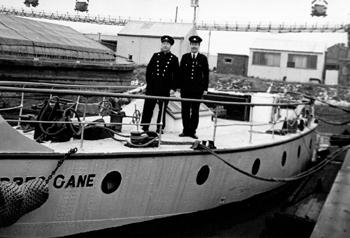 #523 - En service de 1936 à 1967. Long de 19 mètres, capacité hydraulique de 5 450 l/min. Deux membres d'équipage du bateau-pompe dont Dennis Mellery,le barreur, à gauche. Le navire est amarré au Royal Edward Docks. Photographie Coll. Michael MELLERY