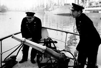 #524 - En service de 1936 à 1967. Long de 19 mètres, capacité hydraulique de 5 450 l/min. Deux membres d'équipage du bateau-pompe dont Dennis Mellery,le barreur, en train de manœuvrer la lance-canon. Photographie Coll. Michael MELLERY