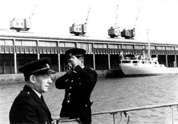 #525 - En service de 1936 à 1967. Long de 19 mètres, capacité hydraulique de 5 450 l/min. Deux membres d'équipage du bateau-pompe dont Dennis Mellery, le barreur (à gauche). Le bateau-pompe se trouve dans les eaux du Royal Edward Docks. Photographie Coll. Michael MELLERY