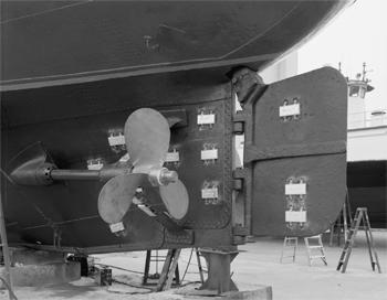 #391 - Bateau-pompe en service à New York de 1931 à 1994. Conservé aujourd'hui par Save Our Ships New York. Ici en cale sèche à Staten Island pour une maintenance  quinquennale. Vue d'un des deux arbres de transmission, son hélice à trois pales et le safran. Les blocs gris que l'on aperçoit fixés sur la coque sont des anodes sacrificielles en Zinc. Elles permettent de protéger la coque contre la corrosion. Photographie Library of Congress, Prints & Photographs Division, HAER NY-335 - 2005